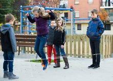 跳在中国人跳跃的有弹性绳索的孩子在围场 图库摄影
