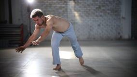 跳在他的手和举的脚上的人-显示capoeira元素 股票视频