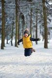跳在冬天森林里的男孩 免版税库存照片