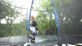 跳在在树中的公园站立的绷床的女孩 影视素材