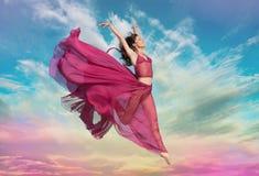 跳在天空中的女孩在日落 图库摄影