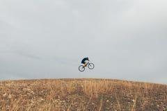 跳在小山的自行车的人 库存照片