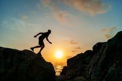 跳在岩石的人在日出 免版税图库摄影
