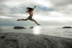 跳在岩石的妇女在Bakovern海滩,开普敦的日落 库存图片