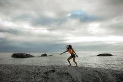 跳在岩石的妇女在Bakovern海滩,开普敦的日落 免版税图库摄影
