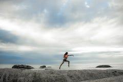 跳在岩石的妇女在Bakovern海滩,开普敦的日落 免版税库存照片