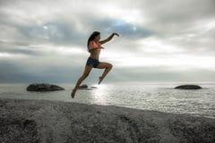 跳在岩石的妇女在Bakovern海滩,开普敦的日落 库存照片