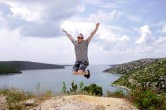 跳在幸福和在背景中的年轻人是海 免版税库存照片