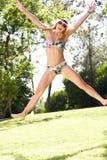 跳在庭院里的妇女佩带的比基尼泳装 免版税库存照片