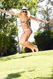跳在庭院里的妇女佩带的比基尼泳装 库存图片
