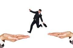 跳在手上的商人 免版税库存图片
