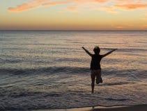 跳在日落海的女孩 免版税库存照片
