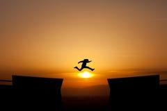 跳在日落的一个空白 免版税库存照片