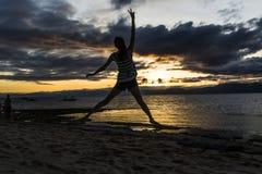 跳在日落的妇女 免版税图库摄影