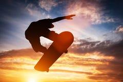 跳在日落的溜冰板者 免版税库存图片
