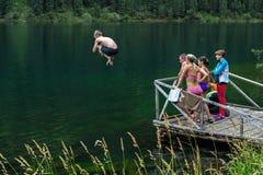跳在有码头的湖的男孩 库存图片
