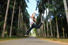 跳在棕榈树之间的女孩 免版税库存照片