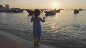 跳在水中的礼服的可爱的小女孩与在海滩飞溅 股票录像