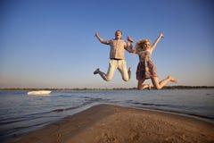 跳在海滩的夫妇 免版税库存照片