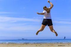 跳在海滩的女孩 库存图片