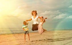 跳在海洋海滩的孩子 免版税图库摄影