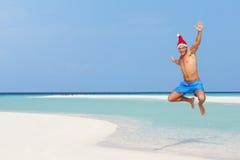 跳在海滩的人戴圣诞老人帽子 免版税库存照片