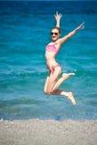 跳在海滩的女孩 免版税库存照片