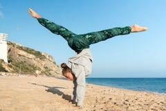 跳在海滩的女孩 免版税库存图片