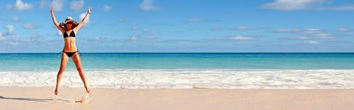 跳在海滩的妇女 免版税库存图片