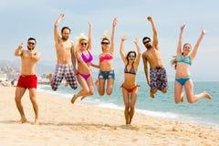 跳在海滩的愉快的人员 库存图片