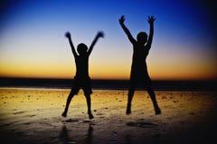 跳在海滩的男孩 库存图片