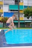 跳在游泳池凉水的男孩  免版税图库摄影