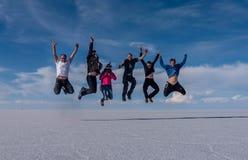 跳在湖撒拉族de Uyuni,玻利维亚的人们 库存图片