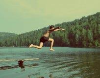 跳在湖-葡萄酒减速火箭的样式的男孩 免版税库存图片