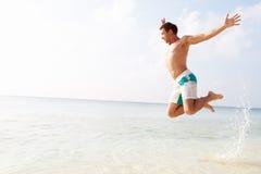 跳在热带海滩的天空中的人 免版税库存照片