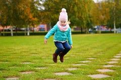 跳在秋天公园的女孩 免版税库存照片