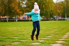 跳在秋天公园的女孩 库存照片