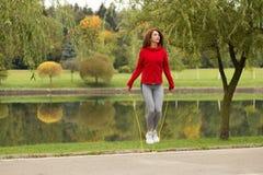 跳在绳索的女孩在公园 免版税库存照片