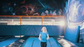 跳在绷床的年轻可爱的运动女孩,执行杂技,舒展,分裂在体育的空气 股票录像
