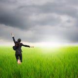 跳在绿色米领域的愉快的女商人   免版税库存图片