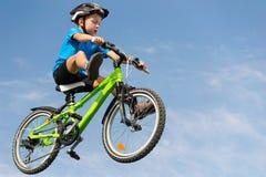 跳在自行车的男孩 图库摄影