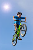 跳在自行车的男孩 免版税库存照片
