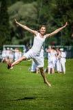 跳在草地的妇女 免版税库存图片