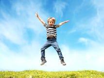 跳在草甸的男孩 免版税库存图片