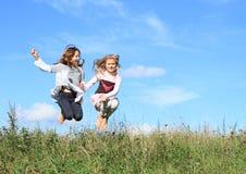 跳在草的女孩 免版税图库摄影
