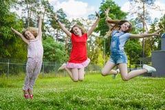 跳在草的孩子在公园 免版税库存图片