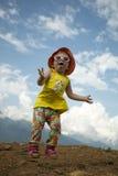 跳在蓝天背景的孩子在山的在夏天 免版税库存照片