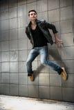 跳在街道墙壁上的英俊的人 免版税图库摄影
