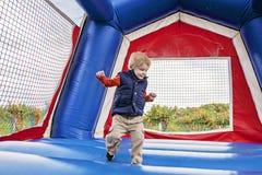 跳在跳动房子里的男孩 免版税库存照片
