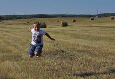 跳在近的干草堆的男孩 图库摄影